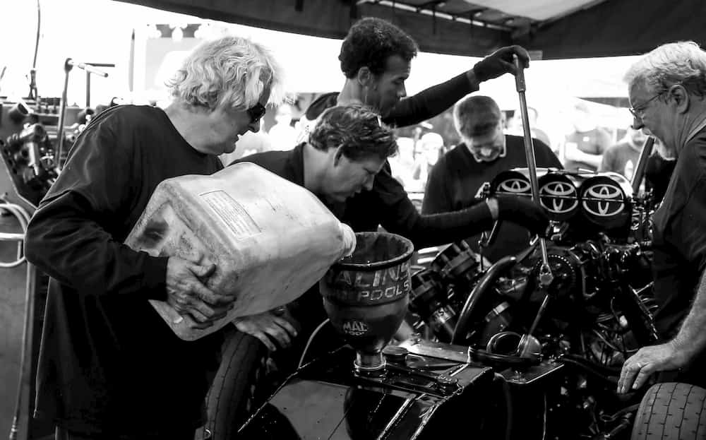men pouring oil to funny car dragster